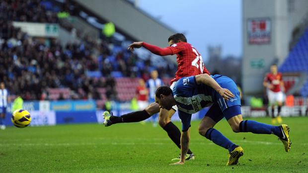 Manchester United's Robin van Persie celebrates his side's second goal during the Barclays Premier League match at the DW Stadium, Wigan. Photo: Martin Rickett, PA Wire
