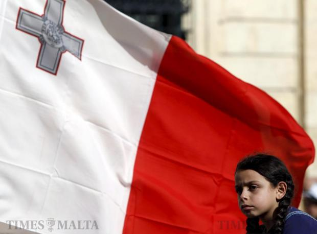 A girl is carried near a Maltese flag during a demonstration against alleged government corruption in Valletta on March 6. Photo: Darrin Zammit Lupi