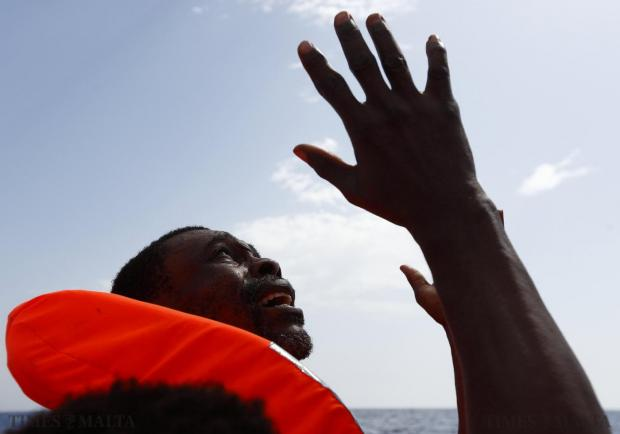 A migrant, who has just been rescued, prays on a Migrant Offshore Aid Station (MOAS) RHIB (Rigid-hulled inflatable boat) whilst being taken to the MOAS ship MV Phoenix some 32 kilometres off the coast of Libya on August 3. 118 migrants were rescued from a rubber dinghy off Libya on Monday morning. The Phoenix, manned by personnel from international non-governmental organisations Medecins san Frontiere (MSF) and MOAS, is the first privately funded vessel to operate in the Mediterranean. Photo: Darrin Zammit Lupi