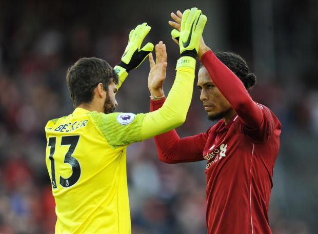 Liverpool's Virgil van Dijk celebrates with Alisson after the match.