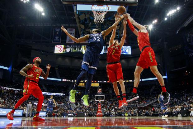 Minnesota Timberwolves center Karl-Anthony Towns (32) reaches for a rebound with Atlanta Hawks forward Ersan Ilyasova (7) and forward Mike Muscala (31) in the second quarter at Philips Arena. Photo Credit: Brett Davis-USA TODAY Sports