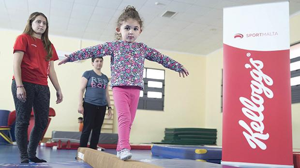 A child on a balance beam at Kirkop Sports Complex assisted by her parent and Sport Malta coach.