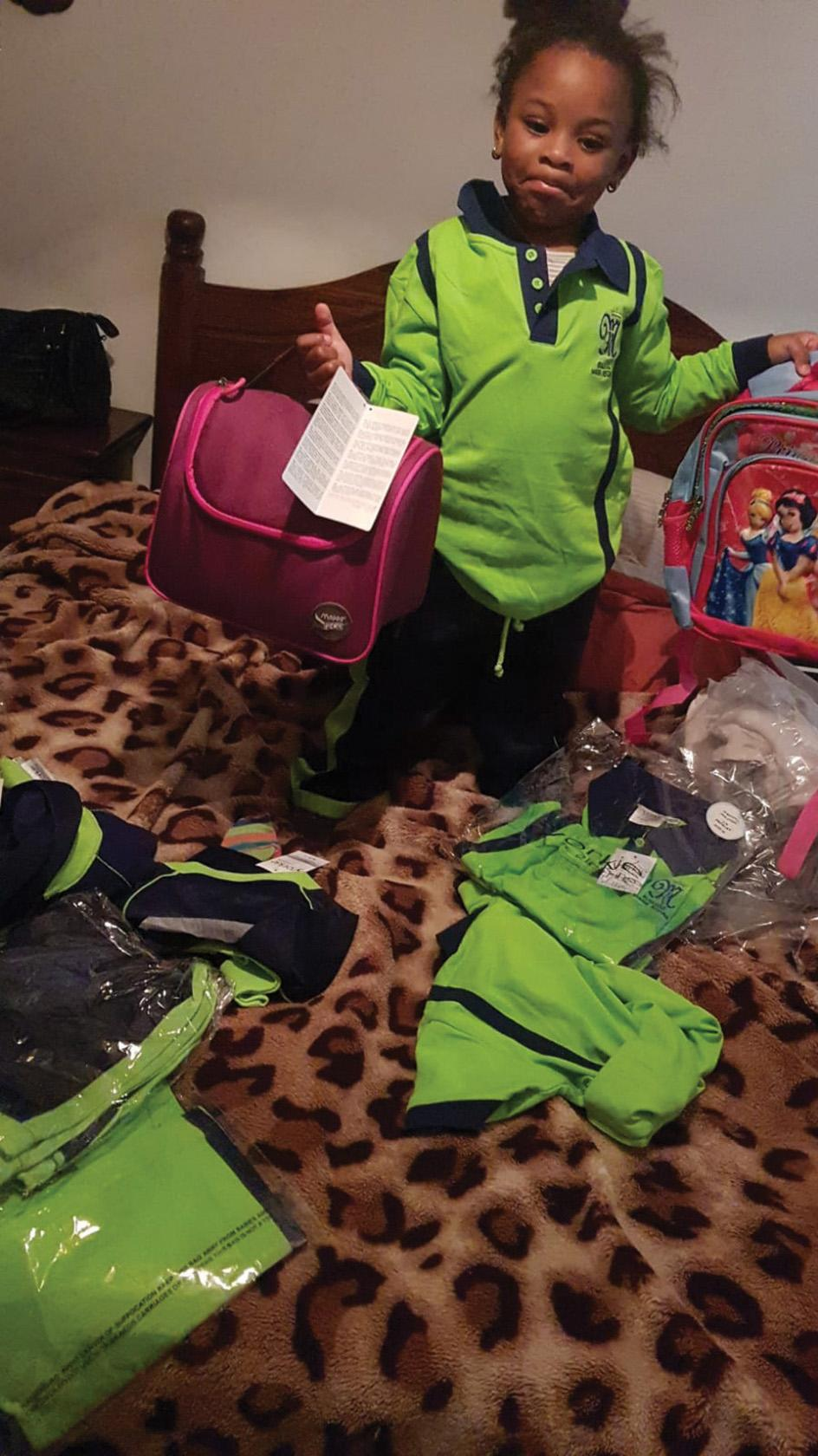 Heavenly Edafe Agoda with her new school uniform and other school items.
