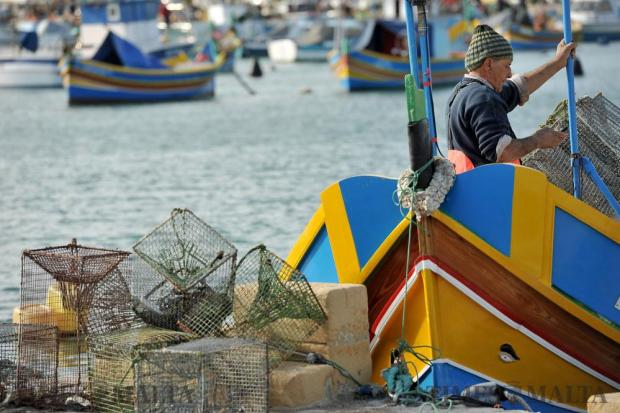 A fisherman sends a text message from his Luzzu in Marsaxlokk on January 4.