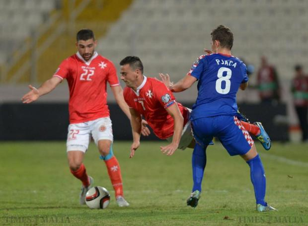 Malta's Clayton Failla (centre) is brought down by Croatia's Marko Pjaca (right) during their UEFA European Championship Qualifying match at the National Stadium in Ta'Qali on October 13. Photo: Matthew Mirabelli