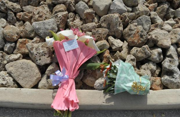 Flowers are laid near Mater Dei Hospital on April 23, during a funeral ceremony of 24 migrants who died after a fishing boat carrying migrants capsized off the Libyan coast. Photo: Matthew Mirabelli
