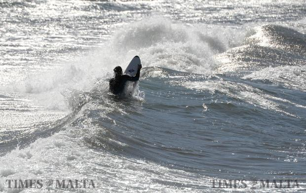 A surfer tries to break through the waves at Ghajn Tuffieha Bay on February 7. Photo: Matthew Mirabelli