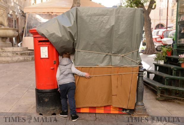 A boy hides between a stall and a post-box in Republic Street Valletta, on December 27. Photo: Matthew Mirabelli