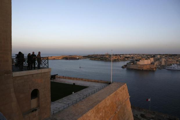 Tourists look at the view of Grand Harbour from the Upper Barrakka Gardens in Valletta at sunset on January 21. Photo: Darrin Zammit Lupi