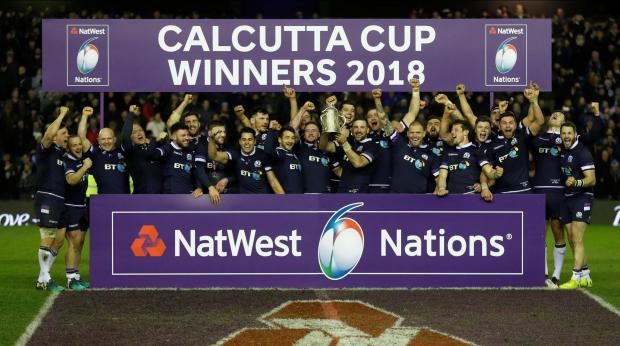 Scotland team celebrate with the Calcutta Cup trophy after victory over England.