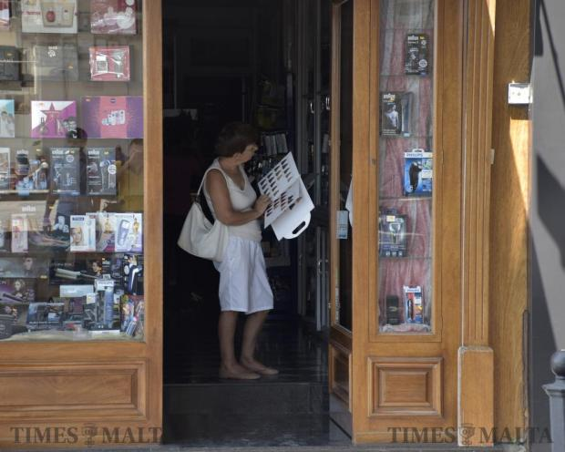 A woman stands in a Sliema shop doorway to make use of daylight to view a shop catalogue after widespread power cuts on August 24. Photo: Mark Zammit Cordina