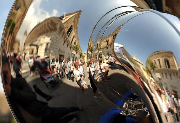 People are distorted in a reflection caused by the curves of a tuba in Valletta on May 9. Photo: Chris Sant Fournier