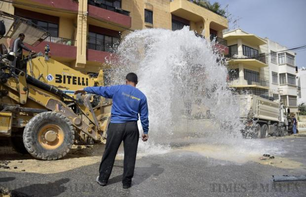 A worker guides a colleague driving a mechanical shovel onto a burst water pipe which let thousands of litres of water down Rue d'Argens in Sliema on March 16. Photo: Mark Zammit Cordina