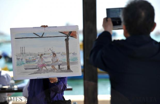 A tourist snaps a picture of his shy wife who hides behind a watercolour painting she just painted of Marsaxlokk bay on April 18. Photo: Chris Sant Fournier