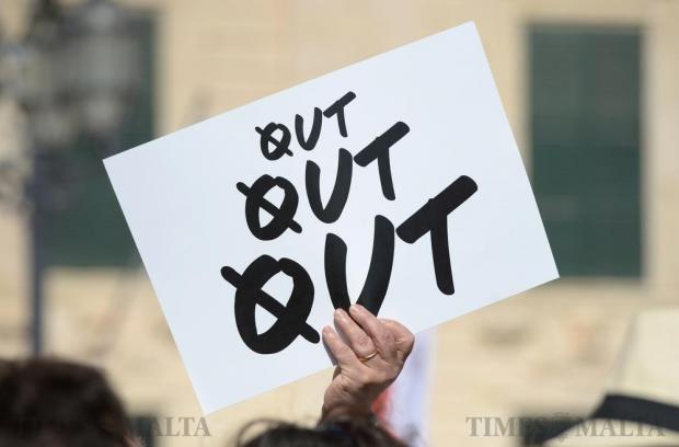 A protestor holds up a placard during a demonstration calling for the resignation of the Prime Minister and two members of the government following the Panama Papers leak scandal outside Castille in Valletta on April 10. Photo: Matthew Mirabelli