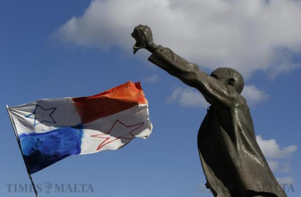 A Panamanian flag flies in the wind near a statue of Maltese pre-independence social reformer Manwel Dimech during a demonstration calling on Prime Minister Joseph Muscat to resign after two members of his government were named in the Panama Papers leak scandal, outside the office of the Prime Minister at Castille Place in Valletta on April 10. Photo: Darrin Zammit Lupi