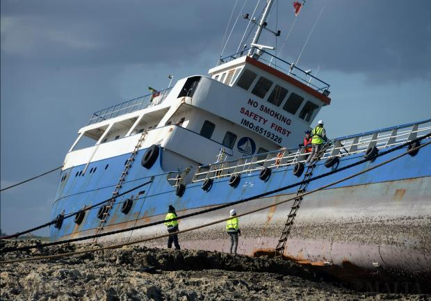 Workers inspect the oil bunkering vessel 'Hephaestus' as it lies on the rocks in St Paul's Bay on February 11. The ship ran aground the previous day. Photo: Matthew Mirabelli