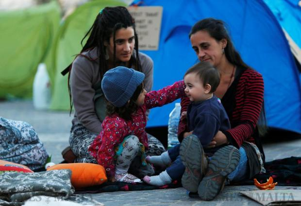 Activists sit with their children outside tents in a camp set up by environmental activists protesting against what they say is over-development throughout the Maltese islands, in front of the Auberge de Castille housing the Office of the Prime Minister in Valletta on May 14. Photo: Darrin Zammit Lupi