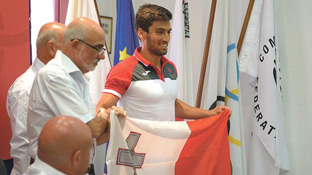 Andrew Chetcuti receives the Maltese flag from MOC president Julian Pace Bonello. Photos: Matthew Mirabelli