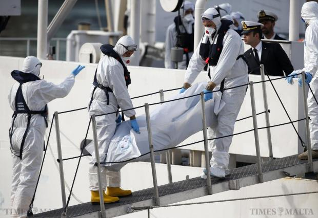 Italian coastguard personnel in protective clothing carry the body of a dead immigrant off their ship 'Bruno Gregoretti' in Senglea on April 20. As many as 800 migrants were feared dead on Sunday after their boat capsized in the Mediterranean, raising pressure on Europe to face down anti-immigrant bias and find money for support as turmoil in Libya and the Middle East worsens the crisis. Photo: Darrin Zammit Lupi