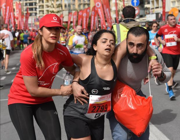 An exhausted runner is helped to the finish line at the end of the Malta Half Marathon in Sliema on February 25. PHOTO: MARK ZAMMIT CORDINA