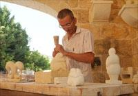A craftsman carving limestone in the workshop at Limestone Heritage.