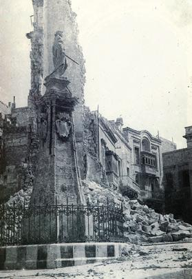 The Victory Monument standing defiantly in front of the ruins of the clock tower after it was destroyed during a German blitz on April 4, 1942.