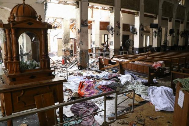 Dead bodies are covered in blankets in this photo taken in the aftermath of one of the blasts that hit a church. Photo: AFP