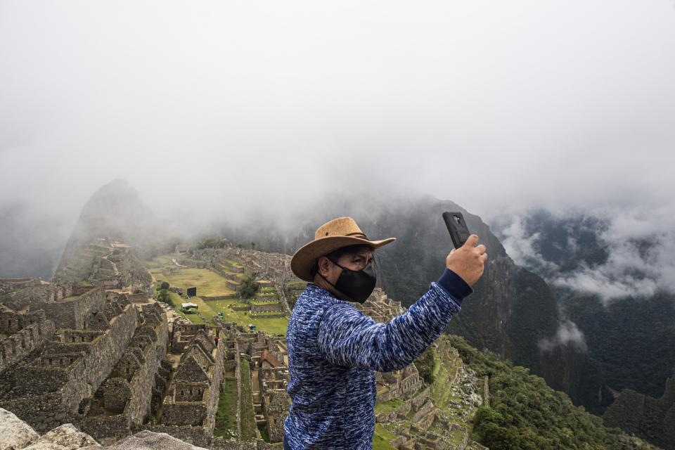 A tourist takes a selfie at the archaeological site in Peru.