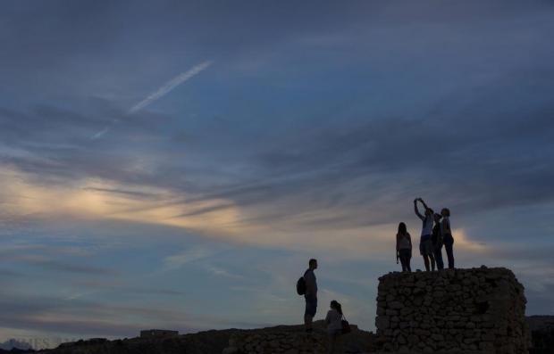 Tourists stand on top of a World War II-era pillbox while waiting for sunset at Ghajn Tuffieha on October 25. Photo: Darrin Zammit Lupi
