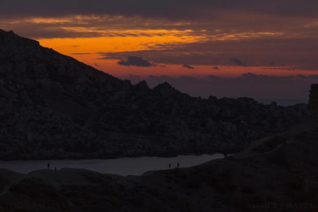 People walk along a ridge overlooking Ghajn Tuffieha Bay at sunset on October 25. Photo: Darrin Zammit Lupi