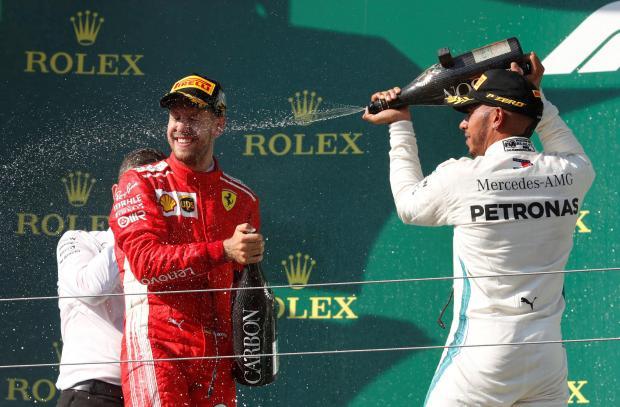 Mercedes' Lewis Hamilton celebrates on the podium after winning the race alongside second placed Ferrari's Sebastian Vettel.