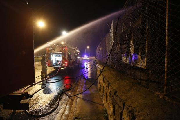 Civil Protection firefighters spray water on prefabricated container houses after fire broke out at the Hal Far open centre for migrants in Hal Far late on December 23. No one was injured in the fire which completely destroyed four prefabricated container houses. Photo: Darrin Zammit Lupi