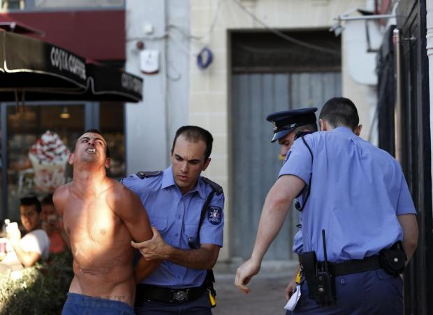 Police officers arrest a heavily-inebriated man after he assaulted a police officer who was trying to escort him away during the St Julian's feast on August 28. Photo: Darrin Zammit Lupi