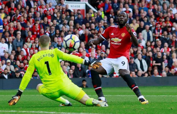 Man. United striker Romelu Lukaku tries to hit the ball past Jordan Pickord.