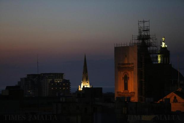 The floodlit steeple of St Paul's Anglican Cathedral and the bell tower of St John's Co-Cathedral, currently undergoing restoration, pierce the dusk sky on June 7. Photo: Darrin Zammit Lupi