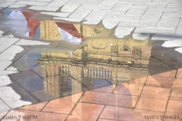 Maltese flags and the Msida Church reflect in a puddle during a protest in Msida on January 17. Photo: Mark Zammit Cordina