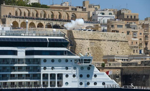 A cannon in Upper Barrakka Gardens fires above a berthed cruise liner on June 20. Photo: Matthew Mirabelli