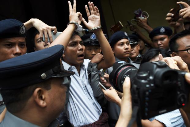 Myanmar journalist Kyaw Soe Oo (C) is escorted by police after being sentenced by a court to jail in Yangon. File photo.
