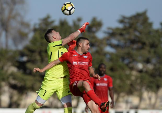 Hibernian's goalkeeper Andrew Hogg punches the ball clear of Balzan's Siraj Arab during their Premier League match at the Hibernian's Stadium in Paola on April 21. Photo: Matthew Mirabelli