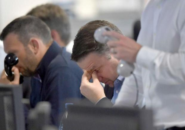 Brokers react on a trading floor at BGC, in the Canary Wharf financial district of London.