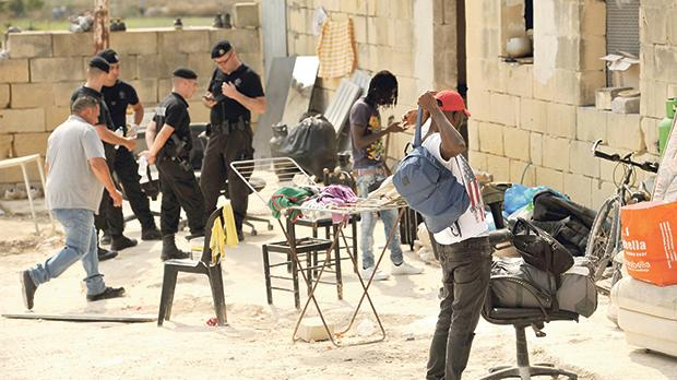 Immigrants packing their belongings before leaving the Qormi farm. Photo: Chris Sant Fournier