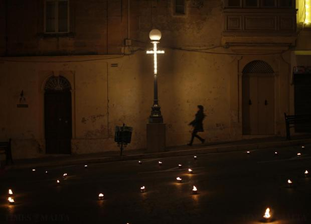 A child runs next to a street lamp adorned with a crucifix in the Siggiewi, on Maundy Thursday on April 2. Photo: Darrin Zammit Lupi