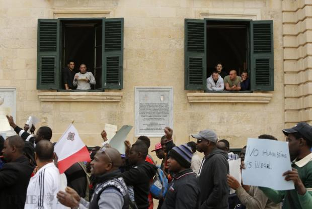 Off-duty soldiers look out of windows of the Presidential Palace as African immigrants demonstrate to call for a change in the system regulating migrant workers, more integration and protection of their basic human rights in Valletta on March 16. Photo: Darrin Zammit Lupi