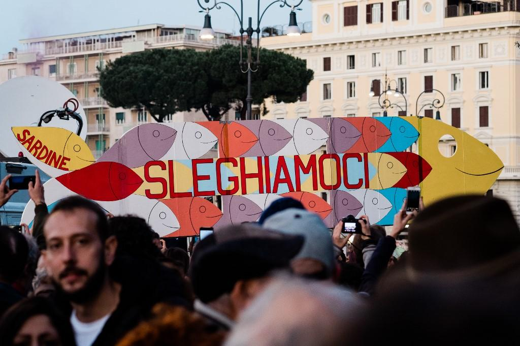 "A big cardboard cutout of a fish with an inscription reading ""Sleghiamoci"" (Untie ourselves) is seen during a flash mob made by ""Sardine"" (Sardines) at San Giovanni square in Rome on December 14, 2019. Photo: AFP"