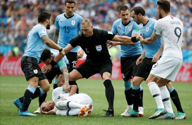 Pitana keeps Uruguay players at bay. Photo: Reuters