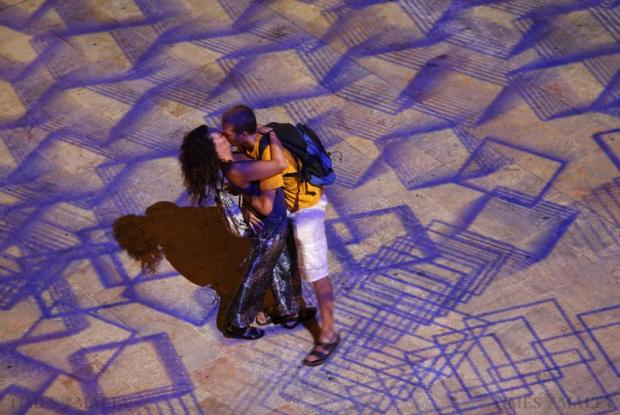 A couple kisses under the projections of Pixels Wave 2015, a giant carpet of moving lights on the ground in an interactive virtual reality installation by Mexican-born experimental and multidisciplinary artist Miguel Chevalier, during the Malta International Arts Festival, at the entrance to Valletta on July 13. Photo: Darrin Zammit Lupi