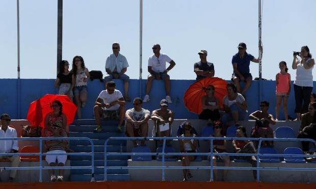 Spectators shelter from the sun while watching the ASA National Swimming Championships at the National Pool in Tal-Qroqq on June 28. Photo: Darrin Zammit Lupi