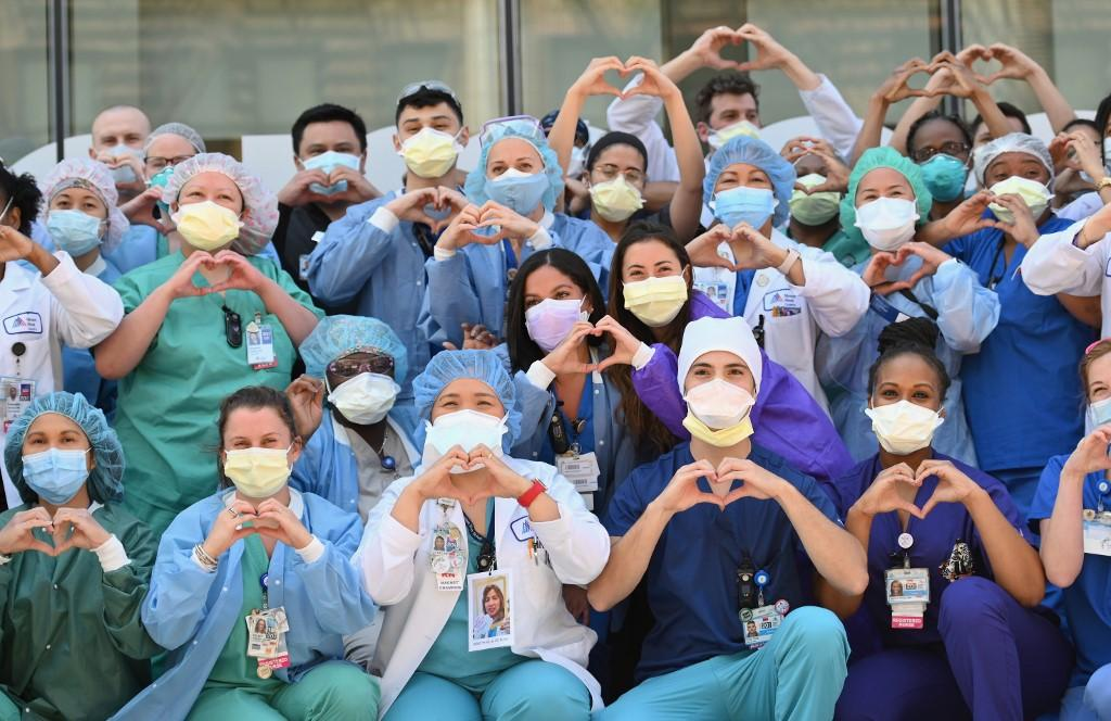 Nurses and healthcare workers gesture hearts in celebration of Nurse Week and International Nurses Day outside Mt. Sinai Oueens in the Queens borough of New York City. Photo: AFP