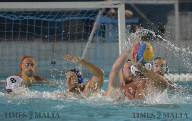 Neptunes' Steven Camilleri holds the ball behind his back before attempting to score against St Julian's during their waterpolo match at the National Pool in Tal-Qroqq on August 22. Photo: Mark Zammit Cordina